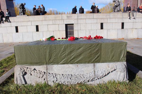 """Mit Planen abgedeckte Steinplatte Sowjetisches Ehrenmal mit der zerstörten Inschrift: """"Die Heimat wird die Helden nicht vergessen"""" und """"1941-1945"""". Foto: Helga Karl 8.11.2015"""