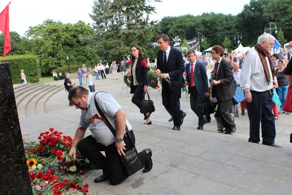 Ein Mann mit Sankt Georgsband kniet, um seine Roten Nelken am Sowjetischen Ehrenmal nieder zu legen. Hinter ihm warten Menschen mit Roten Nelken. Foto: Helga Karl am 22.Juni 2016
