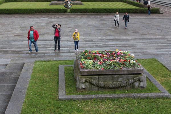 """Steinplatte voll mit Blumen über der Inschrift """"Die Heimat wird ihre Helden nicht vergessen"""". Sowjet. Ehrenmal Berlin. Foto: Helga Karl"""
