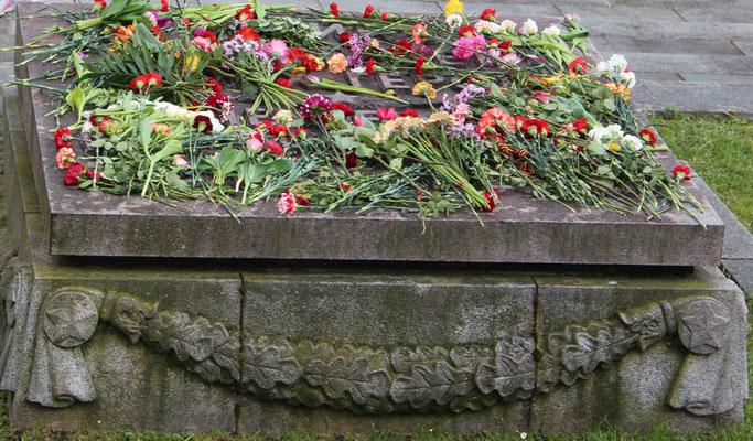"""Mit Blumen belegte Steinplatte: """"Die Heimat wird ihre Helden nicht vergessen"""". Sowjetisches Ehrenmal Berlin. Foto: Helga Karl"""