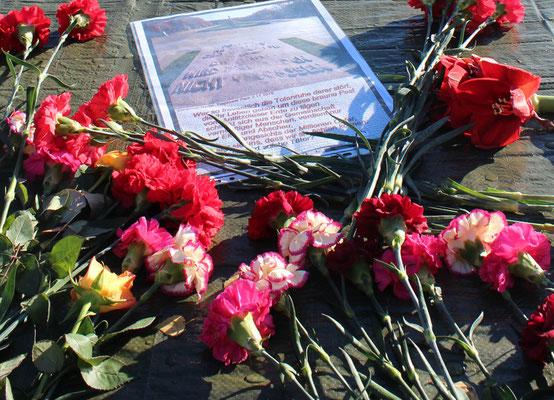 Blumen und ein Protestschreiben auf der durch Vandalismus zerstörten Steinplatte Sowjetisches Ehrenmal. Foto: Helga Karl am 8. November 2015