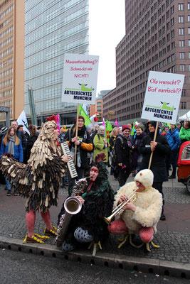 "Musiker als Federvieh verkleidet spielen am Potsdamer Platz vor Plakaten ""Artgerechtes München. Foto: Helga Karl am 21.Jan. 2017"