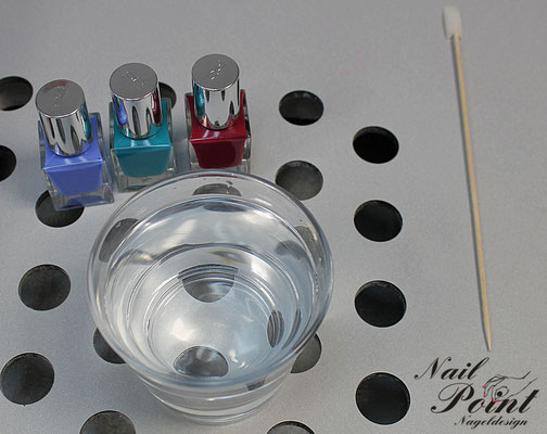 Glas mitdestilliertemWasser und Nagellack in verschiedenen Farben.