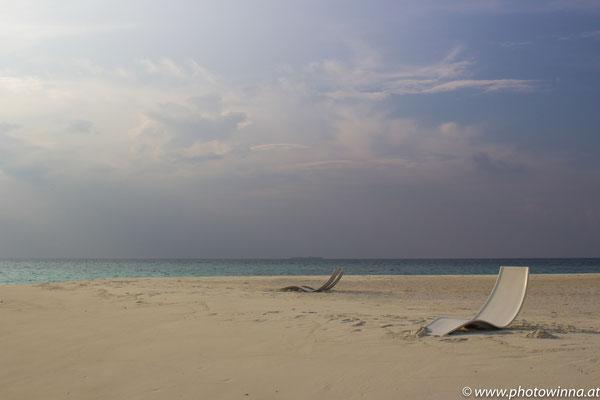 weißer Sandstrand mit Liegen