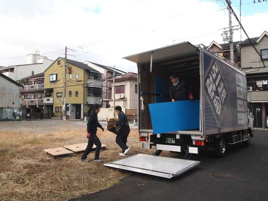 トラックから資材を降ろす作業