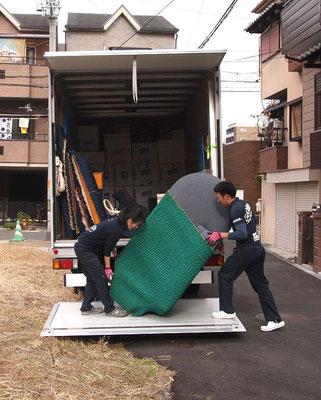 大きな荷物を協力してトラックに載せる
