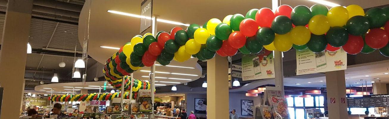 Zur Neueröffnung im Innenbereich eine besonders lange, spiralförmig gedrehte Girlande. Viele unterschiedliche Girlandenmuster und -farben möglich. Marktkauf.