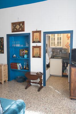 Sala - Le mensole blu cicladico e l'ingresso all'angolo cottura visto dalla camera da letto principale