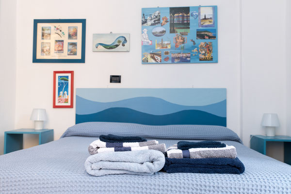 Main Bedroom - Double bed, other marine style paintings, and towels offered to our guests