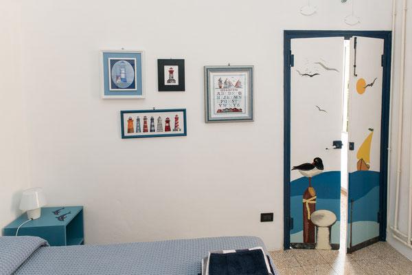Camera da letto principale - Dipinti e quadri in stile marinaro, porta dipinta a mano e letto matrimoniale