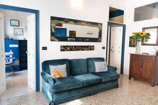 Sala - Vista generale con il divano blu, specchi, cuscini ricamati a mano e gli ingressi alle 2 camere da letto