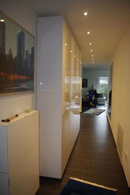 Der Garderobenschrank in Lack weiß Hochglanz schmiegt sich schmal an die Wand im langen, aber engen Flur einer offenen Penthauswohnung.
