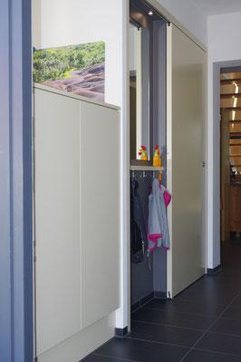 Ensemble aus halbhohem Aufbewahrungsschrank, Spiegel mit kleiner Kindergarderobe und Schiebetüre vor dem Kellerabgang.