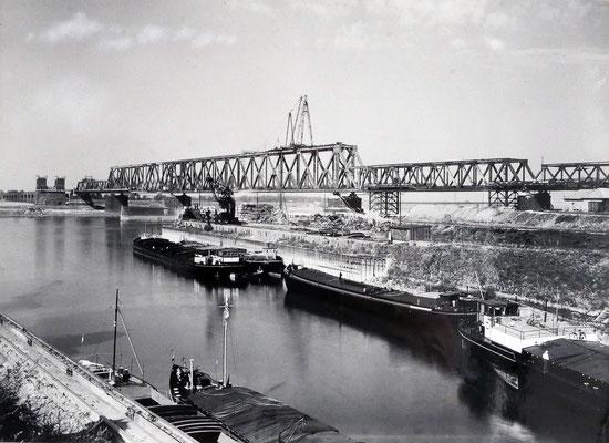 Quelle: Stadtarchiv Duisburg, Die neue Eisenbahnbrücke 1949. Blick von der rechten Rheinseite über den Kultushafen.