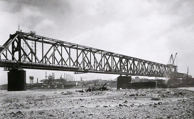 Quelle: Stadtarchiv Duisburg, Die neue Eisenbahnbrücke 1949. Blick von der linken Rheinseite, im Hintergrund unter der Brücke die Niederrheinische Hütte.