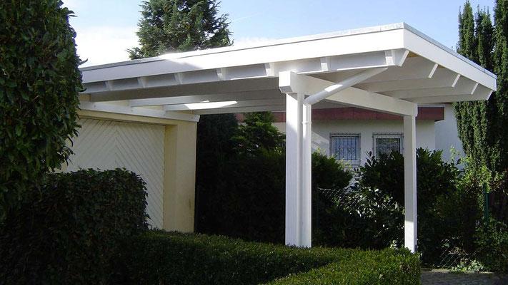 Beispiel Nr. GD4   Weißes Einzelcarport Flachdach vor einer Garage. Mittig vor dem Garagentor wurde ein Glas-Dachaufsatz montiert.