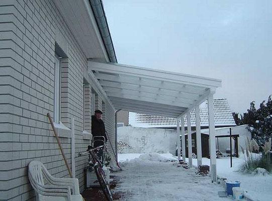 Beispiel-Nr. LDS-17   Weißes LANDSHUT-Carport mit Wandanschluß. Transparente Trapezplatten als Komplett-Eindeckung wegen der überbauten Fenster.
