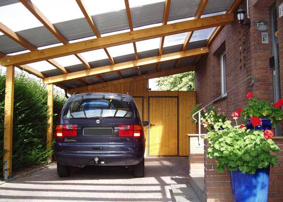 Beispiel-Nr. LDS-12   Eine gute Lösung bei überbauten Türen und Fenstern:   LANDSHUT Carport mit Dachschräge. Farbgebung KIEFER. Dachbelag mit Stahl-Trapezplatten im Wechsel mit Lichtplatten.