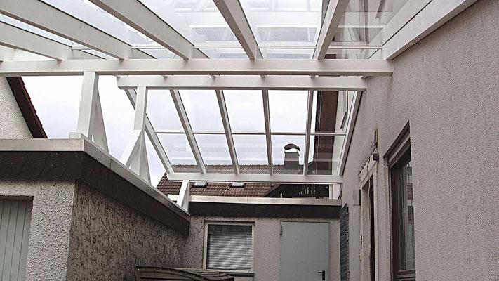 Beispiel Nr. GD3.5   Durch die weiße Leimbinderkonstruktion des Doppelcarports sowie die Glaseindeckung entsteht zwischen den Wohnhäusern ein lichtdurchfluteter trockener Platz