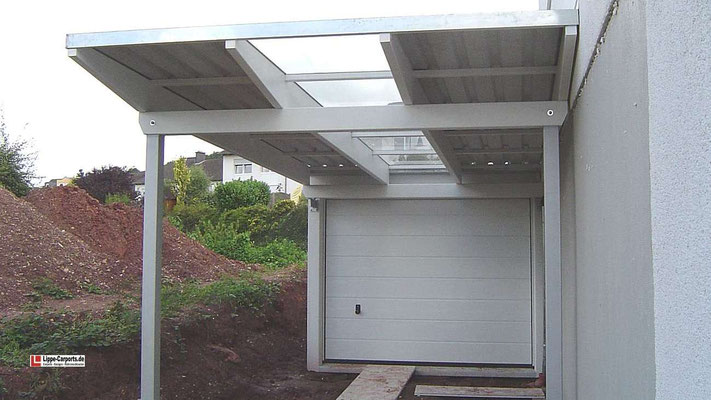 Beispiel Nr. GD24     Einzelcarport INDIVIDUAL in exclusiver Ausführung mit Stahlpfosten und Glasdacheinlage vor einer Betongarage.