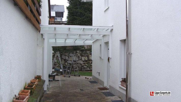 Beispiel Nr. GD29     Individuelles Glasdachcarport in Süddeutschlang zwischen einer Mauer und dem Wohnhaus. Hier war eine transparente Dachvariante Pflicht.