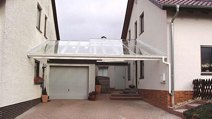 Beispiel Nr. GD3   Glasdach-Carport zwischen 2 Wohnhäusern.  Am linken Wohnhaus  wurde Eingang und Garage mit überdacht, beim rechten Wohnhaus der komplette Eingangsbereich sowie ein dahinterliegender Geräteschuppen.