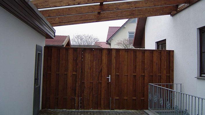 Beispiel Nr. GD9.2.   Als Auflager für dieses Carport dient die bestehende Garage. Rückseitig wurde ein Sichtschutz mit Tür montiert, der die Farbe der Überachung aufnimmt.