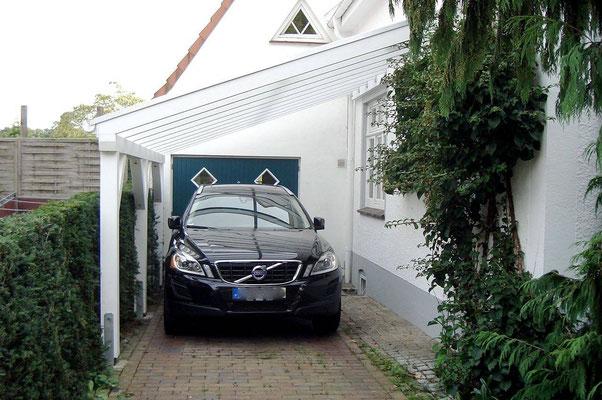 Beispiel-Nr. WA-22   Wandcarport KÖLN in weiß mit Stegdoppelplatten glashell an einem Einfamilienhaus. Die Schräge ergibt sich aus der Höhe der Hausfenster.