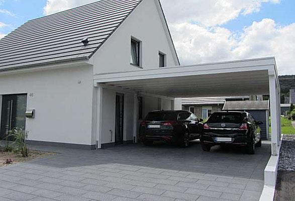 Beispiel-Nr. M-14   Doppelcarport MÜNCHEN an einem Einfamilienhaus im Lippischen. Einpassung der Carportbreite genau zwischen Betonmauer und Hauswand.