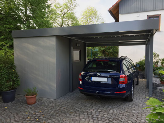 Beispiel-Nr. ST-Y  Einzelcarport mit seitlich gestellter Anbaukammer mit Dekorputz-Glattwänden. Die Kammer erhält zusätzlich ein Fenster aus dem umfangreichen Zubehörprogramm für Stahlcarports.