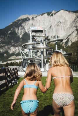 © Ötztal Tourismus Photograf Christoph Schöch Bildbeschreibung Ötztal, AREA 47, Kinder, Springen, Sprungturm, Wiese, Sommer, laufen, Mädchen, Berge, blauer Himmel, Ötztal Premium Card