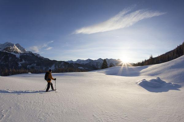 © Ötztal Tourismus Photograf Bernd Ritschel Bildbeschreibung Ötztal, Ochsengarten, Schneeschuhwandern, Mann, Schnee, Spur, Winter, Wald, Bäume, Berge, blauer Himmel, Sonnenstrahlen