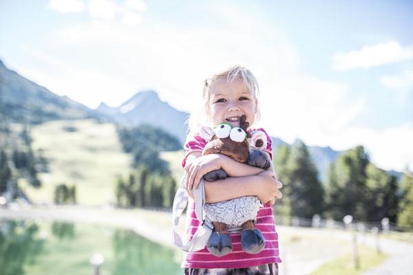 © Ötztal Tourismus Photograf eye5.li - Daniel Zangerl Bildbeschreibung Ötztal, Region Oetz, Almenregion Hochoetz, WIDIVERUM Hochoetz, Sommer, Familie, Kinder, WIDI Rucksack, See, Wasser, Mädchen, Berge