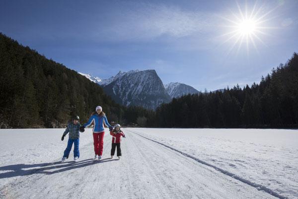 © Ötztal Tourismus Photograf Bernd Ritschel Bildbeschreibung Region Oetz, Eislaufen am Piburger See, Winter, Familie, Sonne, See, Wald, Bäume, Berge, Acherkogl, Eis, Frau, Kinder, Schnee