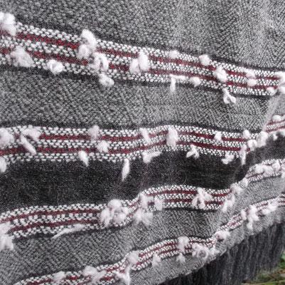 kleine Fadenenden ragen aus dem Tuch, ähnlich der Samenständer der Waldrebe