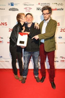"""Nicolas Christitch & Katrin Vierkant mit ihrem Laudator Christof Jessen und dem HANS für """"Recorded. Live In Hamburgs Plattenläden"""" (Buch)"""
