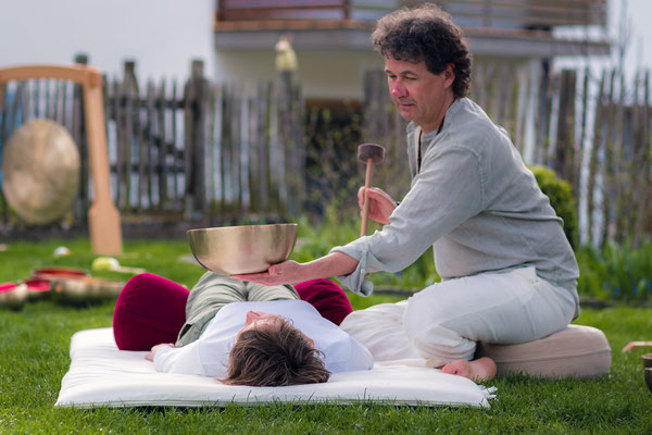 Klangschale auf dem Körper bei der Klangmassage im Garten