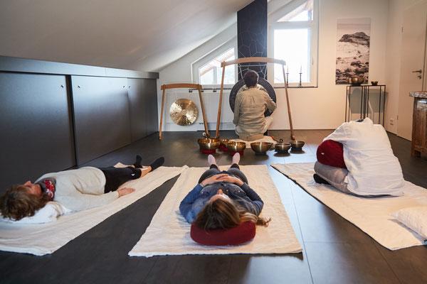 Entspannte Personen bei Fantasiereise mit Klangschalen und Gong