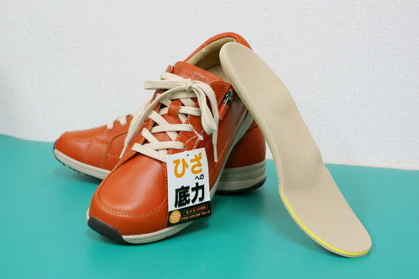 「ひざを守る」がキャッチコピーのアサヒ・メディカルウォークLB(オレンジ)と、オーダーインソール。