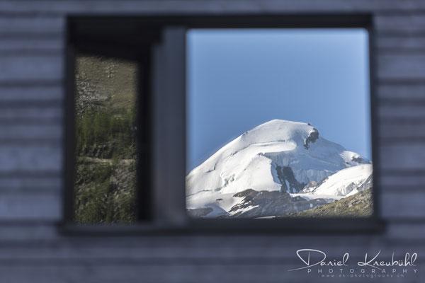 Allalinhorn spiegelt sich im Fenster des Aqua Allalin