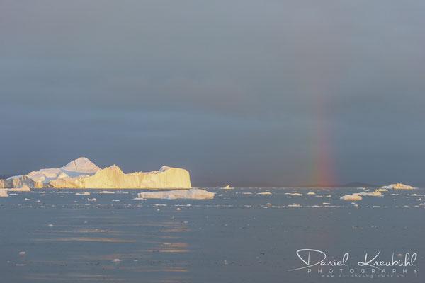 Gigantischer Eisberg bei Sonnenuntergang mit Regenbogen am Icefjord Ilulissat