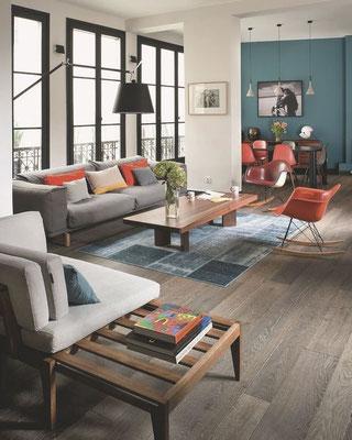 Salon lumineux mêlant décoration moderne et design avec des touches de couleurs chaudes.