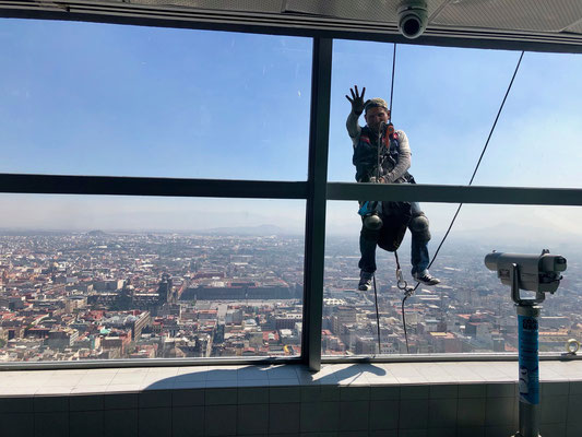 The window cleaner hanging in a normal climbing rope 300m above Mexico City in the Torre Latino