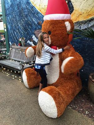 Lynn hugging a giant Teddy in Hanalei Shopping Street