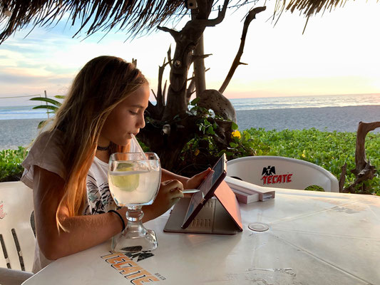 home work at sunset in a beach bar sipping lemonade