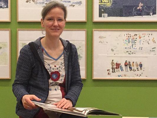 Illustratorin Claudia Posingis vor den Bildern der Preisträgerin Ulrike Jänichen.