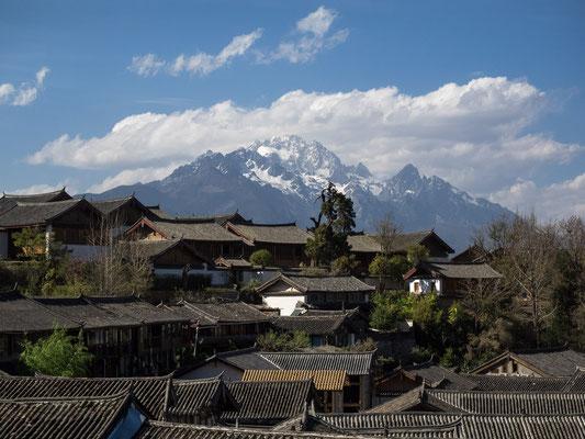 """Ausblick über die Altstadt von LIJIANG 丽江 mit YULONG XUESHAN 玉龙雪山 (""""Jadedrachen-Schneegebirge"""") im Hintergrund."""