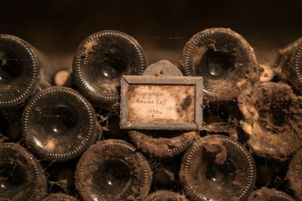 Oude wijnflessen in een wijnkelder in de Bourgogne