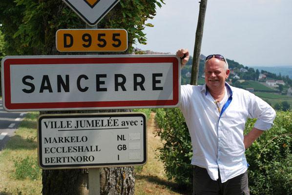 Arend Jan de Wijnman naast het plaatsnaambord van Sancerre met een onderbord waar drie Europese zustergemeentes genoemt worden waaronder Markelo in Nederland.