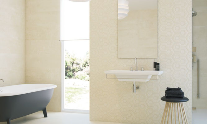 A hexagonal pattern off-white wall tile in a bright and airy bathroom